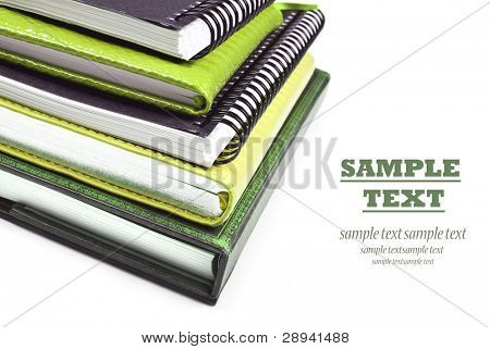Green books stacked up - close up on a white background with space for text