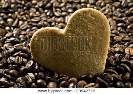 Close up background of a sugar coated heart shaped cookie in  coffee beans   very shallow depth of field and intentional low light
