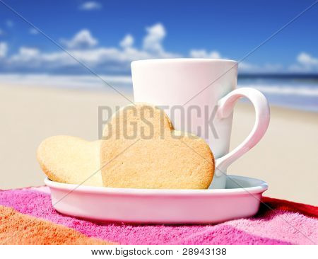 Mug of coffee and heart shaped cookies on a tropical beach
