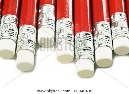 Close up macro of red pencils with white erasers on a white background with space for text