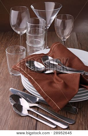 plates stack with cutlery and glasses