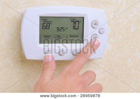 Closeup of a womans hand setting the room temperature on a modern programable thermostat.