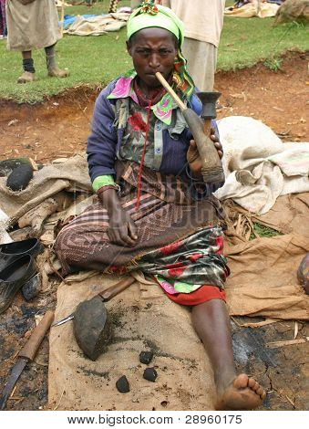 A tribal women from  central Ethiopia  smokes a pipe made from  a bulls horn