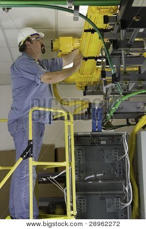 Telecommunication Switch Worker Inspecting Fiber Optic Run