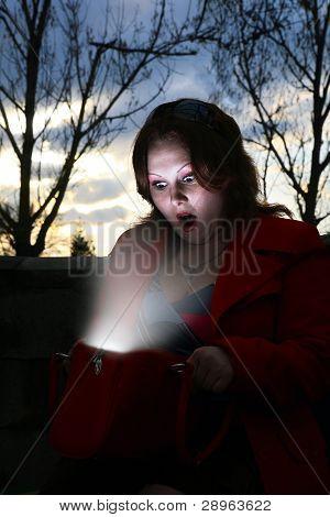 Woman Looking Inside Her Glowing Bag