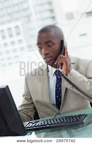 Portrait of a focused office worker making a phone call while using a computer