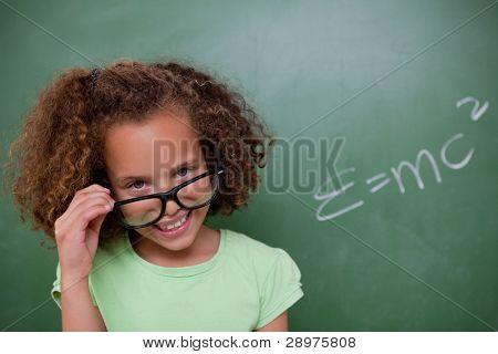 Smart schoolgirl looking above her glasses in front of a blackboard