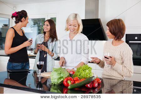 Group of happy female friends in kitchen