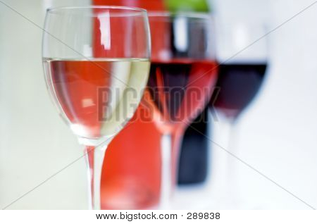 Bottles Of Red, White And Rose Wine With Glasses In Front
