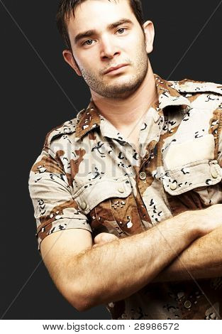 portrait of a serious young soldier standing against a black background