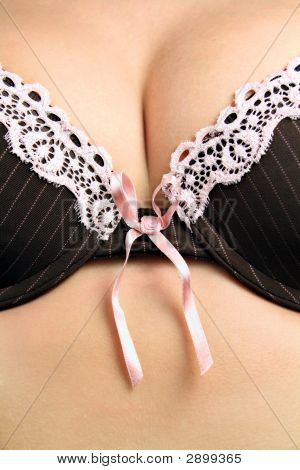 Female Breasts In A Black Bra With A Light Pink Bow