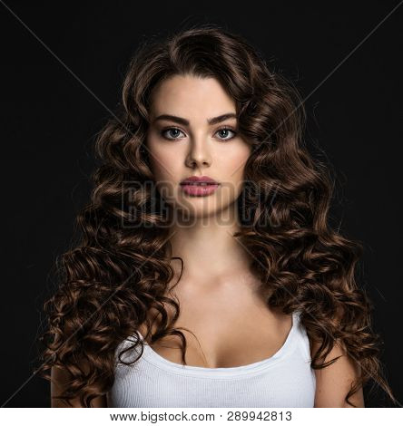 poster of Beautiful young woman with long curly brown hair and  smoky eye makeup. Sexy and gorgeous brunette g