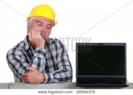 senior craftsman posing next to a laptop