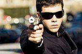 Agent aiming with gun in the middle of the street. Weapon out of focus.