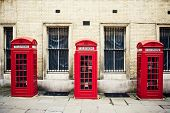picture of phone-booth  - Three red phone boxes over grunge wall background - JPG
