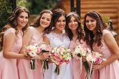 Happy Bride With Bridesmaid Hold Bouquets And Have Fun Outside. Beautiful Bridesmaid In Same Dresses poster