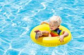 Child In Swimming Pool On Toy Ring. Kids Swim. poster