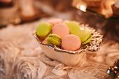 Colorful Macarons Stand In Round Transparent Weight As Part Of Candy Bar Sweet Table. French Macaroo poster