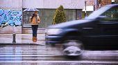 Постер, плакат: Молодая блондинка ждет остановки движения под дождем