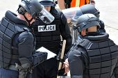 First responders planning tactics - Officers in riot gear plan to keep the peace