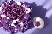 A White Easter Basket Decorated With Purple Flowers And A White Egg With A Purple Flower On A Light  poster
