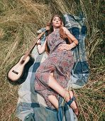 Young Hippie Woman With Guitar Lying On Grass poster