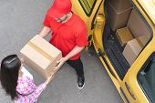 Courier In Red Uniform Takes The Delivery Package From Woman S Hands. Brunette Woman Takes Her Parce poster