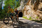 Couple mountain bike rider on electric bike, e-mountainbike rides up mountain trail. Woman and Man r poster