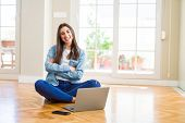 Beautiful young woman sitting on the floor with crossed legs using laptop happy face smiling with cr poster