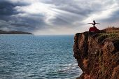 image of cliffs  - Beautiful woman doing virabhadrasana warrior yoga pose on the cliff near the ocean with dramatic sky at background in India - JPG