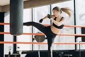 Kickboxing Woman Training Punching Bag In Fitness Studio Fierce Strength Fit Body poster