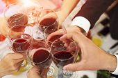 Male And Female Hands With Filled Glasses Of Wine Above The Restaurant Tabletop. Drinking Toasts And poster