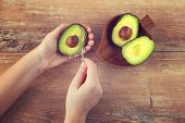Female Hands Holding Spoon And Half Of Fresh Ripe Avocado. Woman Peeling Avocado. Green Avocado On W poster