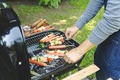 Man Cooking Meat On Barbecue For Summer Family Dinner In The Backyard Of The House.handsome Happy Ma poster
