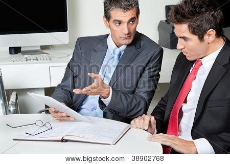 Zwei Geschäftsleute, die mit digitalen Tablet am Schreibtisch in Büro