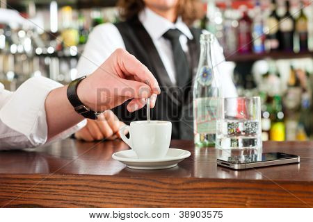 Coffeeshop - barista in cafe with a client, he is drinking coffee