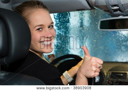 Young woman drives car in wash station cleaning the auto