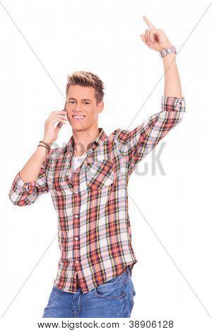 Retrato de un joven casual ganando mientras habla por teléfono y apuntando hacia arriba, aislado en Pentecostés