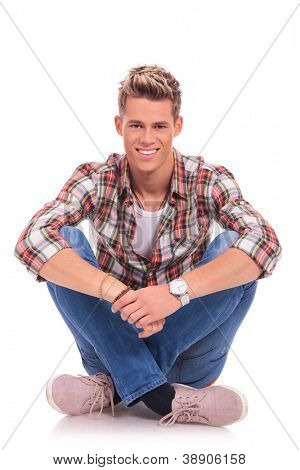 casual young man sitting with legs crossed, in lotus position and smiling to the camera
