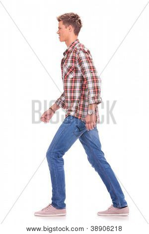 full length side view picture of a casual young man walking forward, isolated on white