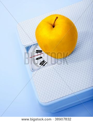 Apple on scale, body weight watching, conceptual image of dieting, calorie count, healthy lifestyle and shape control