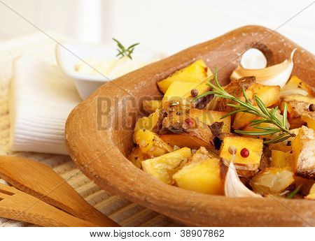 Photo of tasty fried potato with garlic, baked vegetables, french fries with grilled vegetable in wooden plate on the table, healthy food, organic nutrition, restaurant meal, thanksgiving dinner