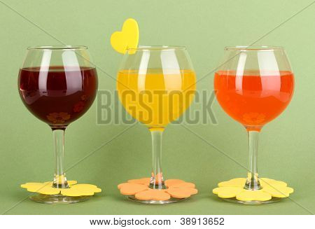 Colorful cocktails with bright decor for glasses on green background