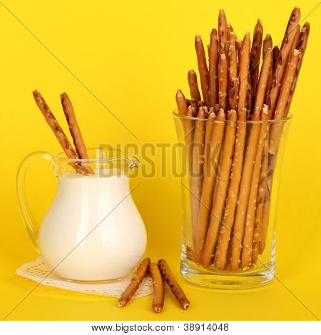 Tasty crispy sticks in glass cup on yellow background