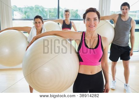 People holding exercise balls at the gym