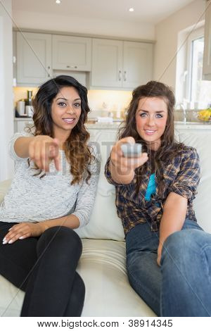 Two women enjoying watching tv holding remote and pointing at screen on sofa