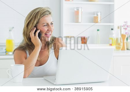 Smiling woman talking on mobile phone in kitchen with laptop