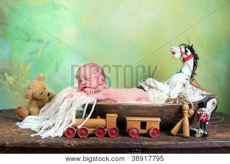 Little baby sleeping in a dough bowl surrounded by antique toys