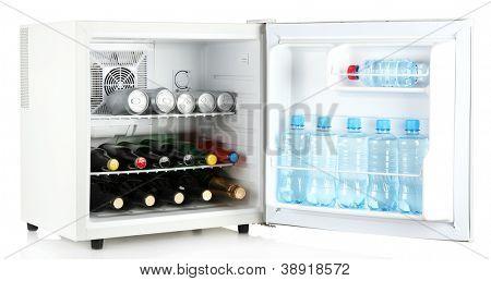 Mini fridge full of bottles of alcoholic beverages and water isolated on white