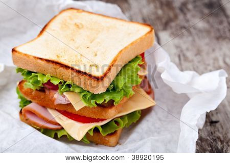 Sandwich with bacon and vegetables on wooden table